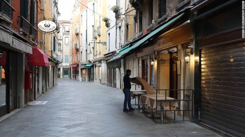 A waiter sets a table in a restaurant on an empty street in Venice, Italy.