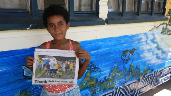 Student holds up newspaper article for Outrigger Fiji Beach Resort walkathon