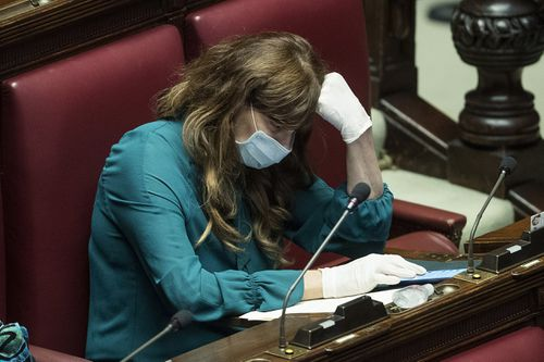 Politician  Maria Teresa Baladini wears a face mask and gloves during a session in parliament on financial relief. Picture: Roberto Monaldo.