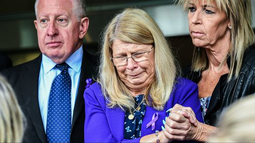 Faye Leveson (centre) is supported by her husband Mark Leveson (left) and a friend at the NSW Coroner's Court. (AAP)