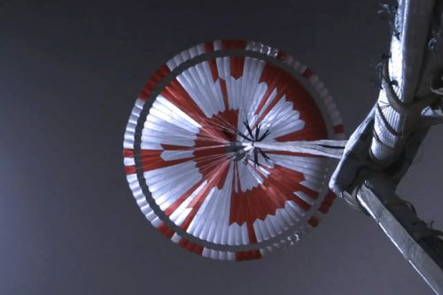 This image from video made available by NASA shows the parachute deployed during the descent of the Mars Perseverance rover as it approaches the surface of the planet on Thursday, Feb. 18, 2021. Systems engineer Ian Clark used a binary code to spell out Dare Mighty Things in the orange and white strips of the 70-foot (21-meter) parachute. He also included the GPS coordinates for the mission's headquarters at the Jet Propulsion Laboratory in Pasadena, Calif. (NASA/JPL-Caltech via AP)