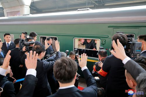 'Hiya, I'm here': Kim Jong-un waves as he pulls into Beijing after his first journey outside North Korea. Picture: AAP