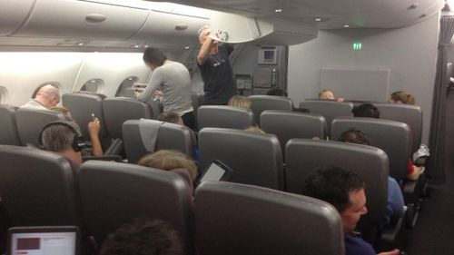 Passengers remain calm after a Qantas plane was forced to make an emergency descent. (Twitter)