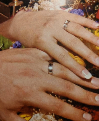 A photo of the couple wearing their rings on their wedding day.