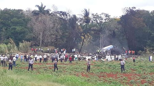 Rescue and search workers on the site where a Cuban airliner with 104 passengers on board plummeted into a yuca field just after takeoff. Picture: AP