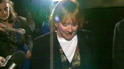Bond's wife, Eileen, is questioned by media as her husband serves time in jail for fraud.