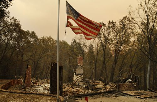 A tattered flag flies over a burned-out home in Paradise, the 1800s town which has seen the worst of the wildfires.
