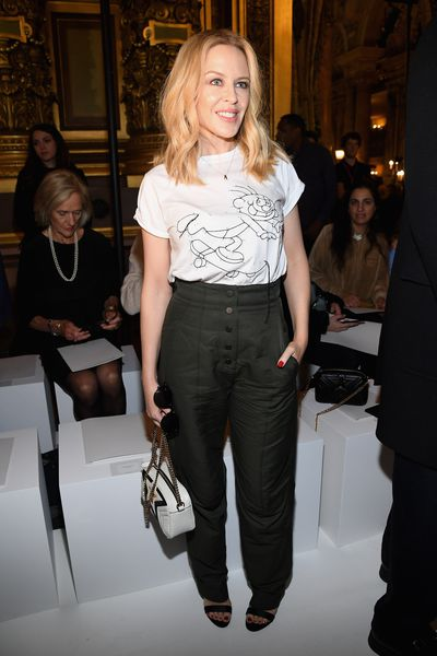 <p>The brightly-coloured, '80s-inspired designs sent down the runway by Stella McCartney at her Spring/Summer '18 show took a backseat when pint-sized Australian singer Kylie Minogue arrived and took her seat in the front-row.</p> <p>The Spinning Around singer kept it cool and casual in a pair of khaki-coloured pants and a printed t-shirt both from the British designer and let her natural beauty do the talking, rocking a bare-faced and dewy lip gloss.</p> <p>Minogue was joined in front-row by an A-list lineup consisting of Alexa Chung, Ellie Goulding and Salma Hayek.</p> <p>See more of Kylie plus a swag of other glamorous A-Listers in our celebrity gallery of Fashion Month front row action.</p> <div>&nbsp;</div>