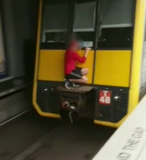 Mitch was shocked when he saw the teen hanging from the back of the train carriage, risking his life.