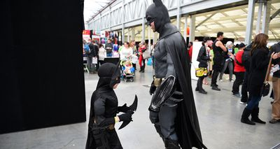 A tiny Batman takes on his adult counterpart on day two of OZ Comic Con in Sydney. (AAP)