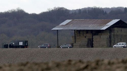 French armed police officers patrol near a farm as they search for suspects. (AAP)