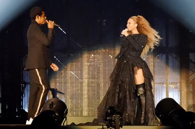 Beyoncé in a sparkling tulle dress and leather over-the-knee boots performing next to husband Jay-Z during the tour.