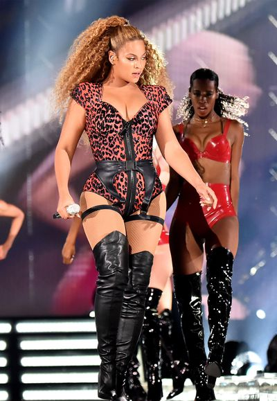 Beyoncé in a leopard bustier and matching coat, performing during her 'On The Run' tour.