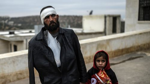 An injured Syrian man who just arrived on the Syrian side of the Bab al-Hawa border crossing between Syria and Turkey waits with his child outside a hospital on December 16, 2016. (AFP)