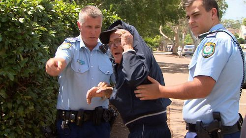 Outside of Sutherland Local Court today, the 78-year-old threw his walking stick at waiting media and was guided away by police (Supplied).