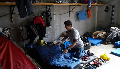 Kevin Roney Hernandez Melgar arranges his bedding in his sleeping area at the El Barretal migrant shelter in Tijuana. Melgar is among 12 men who share a living space at the shelter.