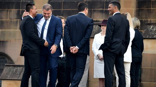 Mourners, including Socceroos coach Ange Postecoglou, gather outside the church. (AAP)