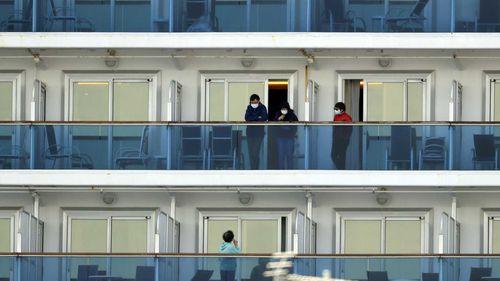 Passengers speak on balconies of the quarantined Diamond Princess cruise ship docked at a port in Yokohama, near Tokyo.