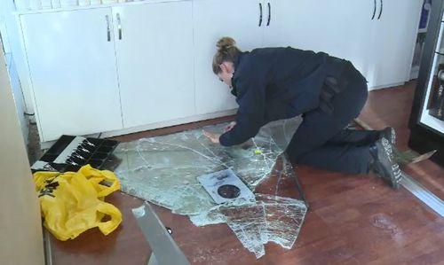 Forensic detectives check for finger prints on the broken glass. (9NEWS)