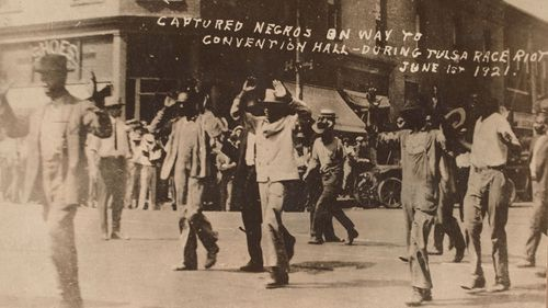 Men walk with their hands raised during the Tulsa massacre on June 1, 1921. (Image gift of Cassandra P. Johnson Smith)