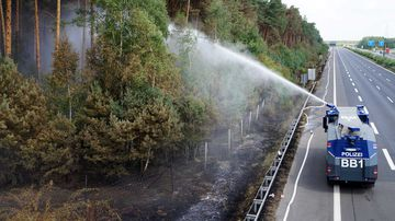 A police water cannon works to extinguish a forest fire that has broken out in the wood within the Potsdam and Fichtenwalde triangles. (AAP)