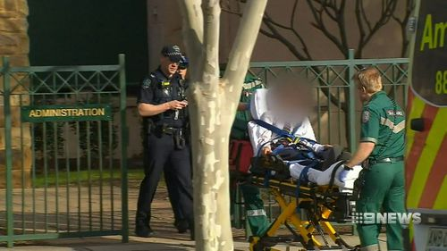 The alleged victim was seen being rushed into an ambulance on a stretcher. Picture: 9NEWS