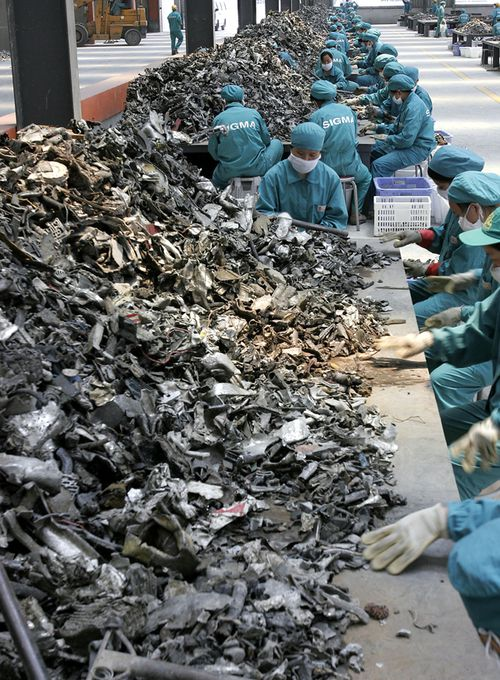 Chinese workers sellect car part scrap to collect aluminum for recycling at a smelting plant in the outskirts of Shanghai. (AAP)