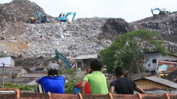 A Sri Lankan boy who survived the garbage dump collapse surveys the damage. (AFP)