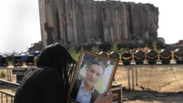 A relative of a victim who was killed in the massive blast last year at the Beirut port reacts and holds his portrait.