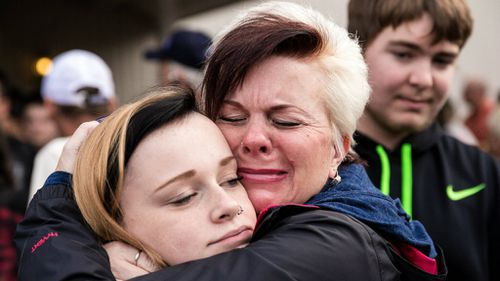 A student is embraced after the shooting. (AAP)