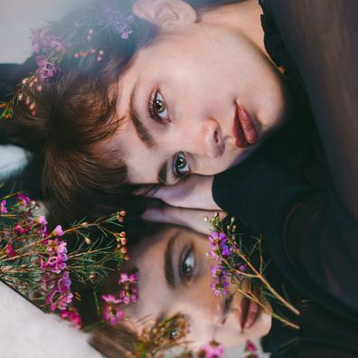 Woman lying on mirror, woman looking in the mirror, flowers