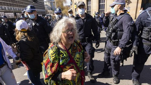A woman surrounded by police near Victoria Park, Sydney.