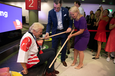 Staff help Sir Richard Branson up off the conveyor belt with oversized chopsticks.