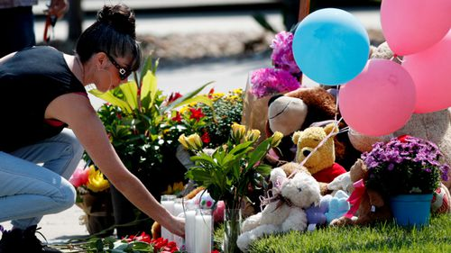 A woman leaves a tribute outside the home of the Watts family.