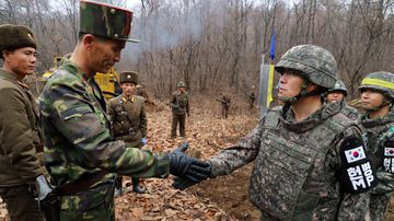 soldiers from the two Koreas shake hands as they gather at Arrowhead Ridge, a site of fierce battles in the 1950-53 Korean War, to build a tactical road across the Military Demarcation Line inside the Demilitarized Zone (DMZ).
