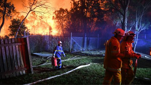 Firefighters fight flames close to homes in Corryton Court, Wattle Grove. (AAP)