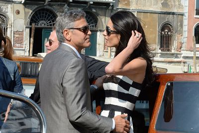 """George Clooney and human rights lawyer Amal Alamuddin swept into the floating city on Friday, riding a water-taxi dubbed """"Amore"""" down Venice's Grand Canal to cheers from fans. <br/><br/>While Clooney beamed, Amal wore a bold black-and-white striped Dolce & Gabbana dress... which totally got TheFIX's tick of approval."""