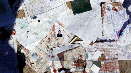 Bloodstained voters' registration papers are seen on the ground at the scene of the attack. (EPA)