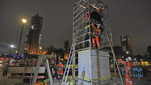 Scaffolders erect boarding around the statue of Sir Winston Churchill at Parliament Square, in London, Thursday, June 11, 2020, following Black Lives Matter protests that took place across the U.K. over the weekend