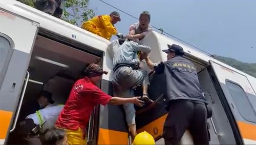 A passenger is helped to climb out of a derailed train in Hualien County in eastern Taiwan.