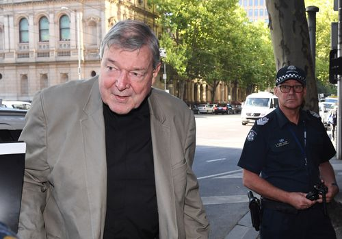 Cardinal George Pell (left) arrives at the Melbourne Magistrates Court in Melbourne this morning. (AAP)