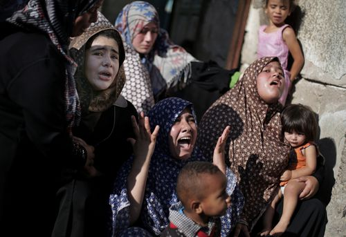 Palestinian relatives of four boys from the same extended Bakr family, grieve during their funeral in Gaza City, Wednesday, July 16, 2014. (AAP)