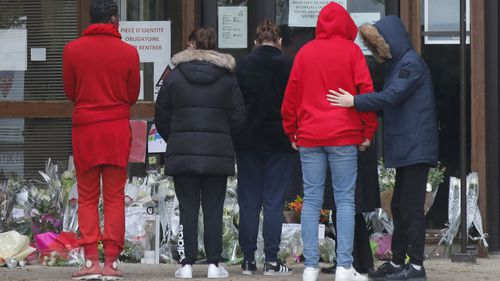 School children pay homage to the slain history teacher outside a school Saturday, Oct. 17, 2020 in Conflans-Sainte-Honorine, northwest of Paris
