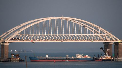 A Russian tanker under the the Kerch bridge blocks the passage to the Kerch Strait near Kerch, Crimea. The Ukrainian Security Service (SBU) said in a statement Thursday July 25, 2019, that it has seized the Russian tanker moored in a Ukrainian Black Sea port. (AP Photo)