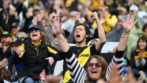 Tigers fans react to an early goal while watching the screens at the Punt Rd. Oval.