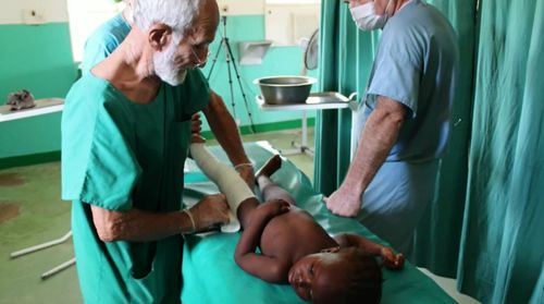 Dr Ken Elliot treats a child in Burkina Faso. (Image: GBS Institute)