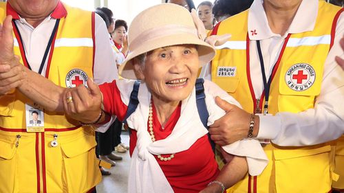 South Korean Lee Geum-seom, 92, is helped by Red Cross officials as she arrives to take part in family reunions with her North Korean family members. (AAP)