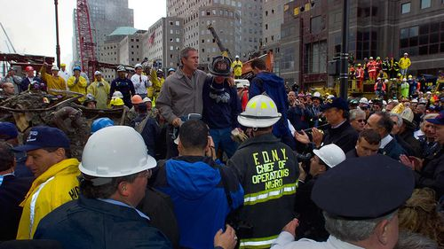 President George W Bush speaks to a group of firefighters amidst the rubble of the World Trade Centre.