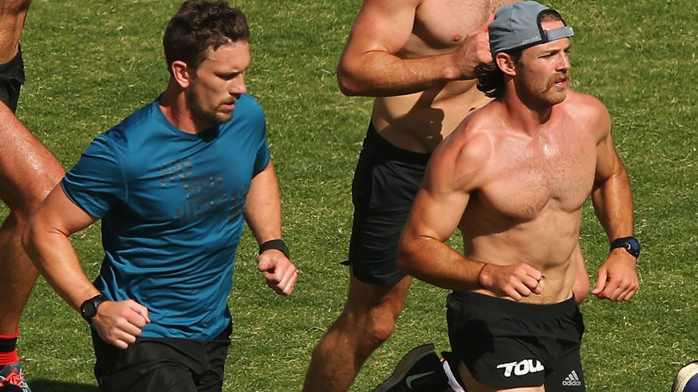 Heath Hocking (L) and Travis Colyer training with other banned Bombers players. (Getty)
