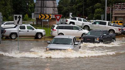 Trucks attempt to drive through a flooded intersection in Youngsville. (AP)